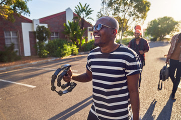 Happy young male musician with tambourine on sunny street