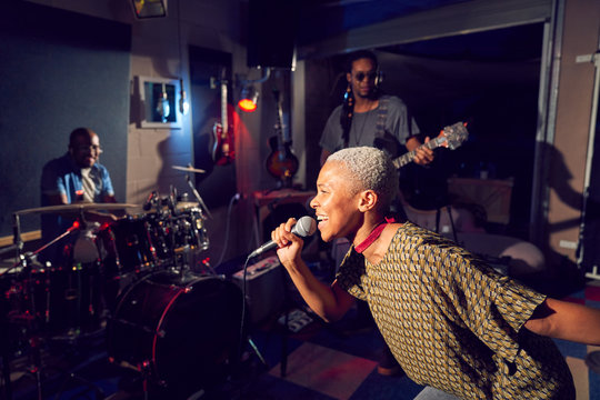 Female musician singing into microphone in recording studio