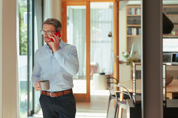 Businessman talking on smart phone and drinking coffee at home