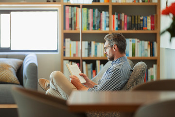 Man relaxing, reading book in living room