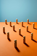 Wooden pawn chess pieces on orange surface