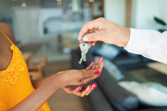Close up man giving house keys to woman