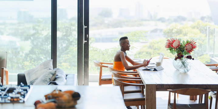 Young woman using smart phone and laptop, working from home at dining table