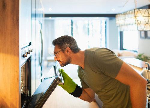 Man cooking, opening oven door in kitchen