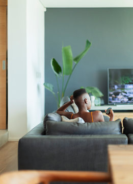 Young woman with remote control watching TV on living room sofa
