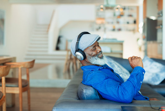 Happy man with headphones listening to music on living room sofa
