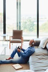 Man wearing headphones using digital tablet at home
