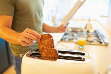 Close up man making toast and reading newspaper in morning kitchen