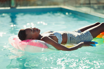 Serene young woman laying on inflatable raft in sunny swimming pool