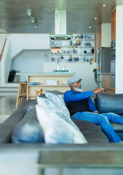 Man with remote control watching TV on living room sofa