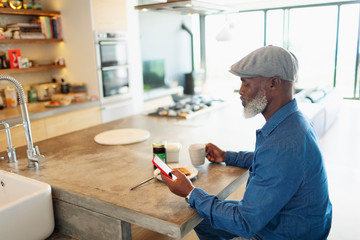 Man enjoying breakfast and using smart phone in morning kitchen