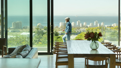 Man standing on sunny patio with scenic view of ocean
