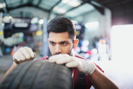 Focused male mechanic examining tire in auto repair shop