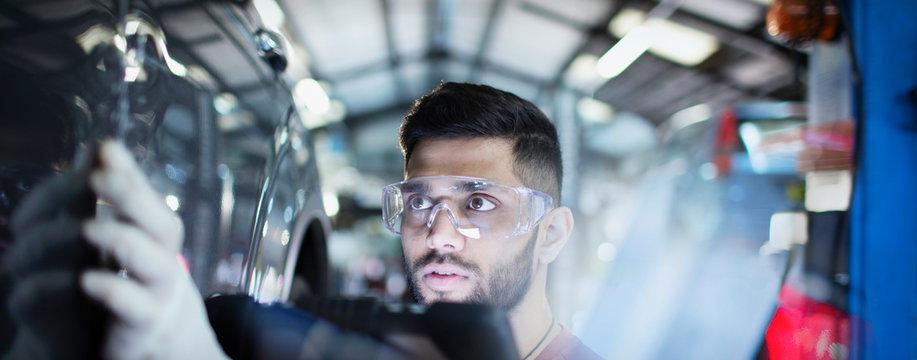Focused male mechanic examining car in auto repair shop