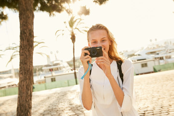 A girl making photos in Barcelona in the sun with palms