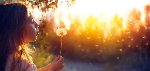 Obraz Little Girl Blowing Dandelion Flower At Sunset - Defocused Background  - fototapety do salonu