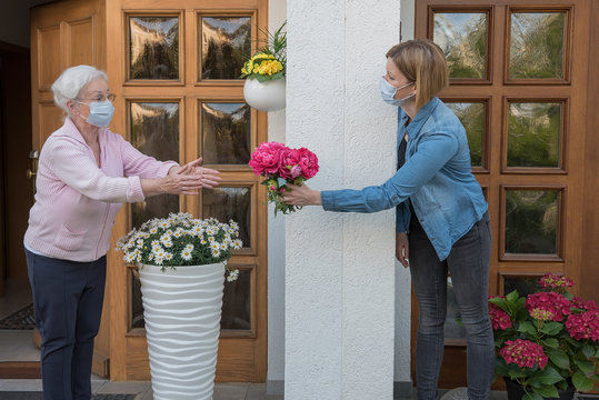 Senior woman with face mask gets flowers from neighbor woman