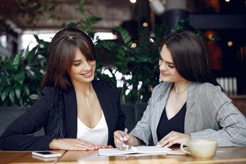 Wall Mural - Two beautiful women working. Friends in a cafe. Women use the notebook