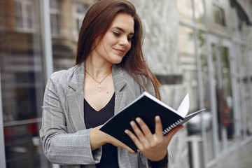 Wall Mural - Beautiful woman working. Busineswoman in a stylish clothes. Lady use the notebook