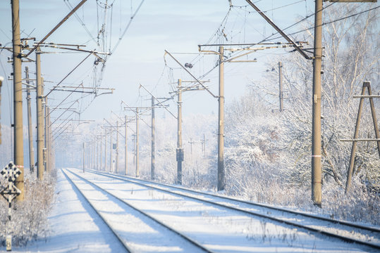 Train tracks in winter with frost covering around