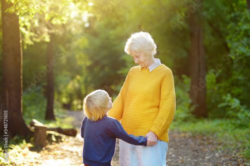 Loving grandson tenderly embracing his joyful elderly grandmother during walking at summer park. Mother's day holiday.