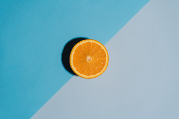 Sliced orange on colorful backgrounds with copy space. Short hard shadow, flat lay. Summer food concept