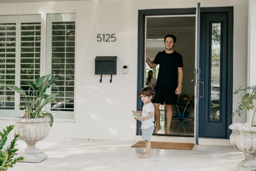 Young man in front of a door with toddler