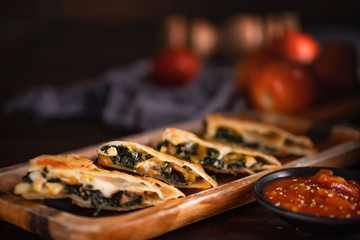 mexican food background of sliced chicken quesadilla with sauce in dark tone