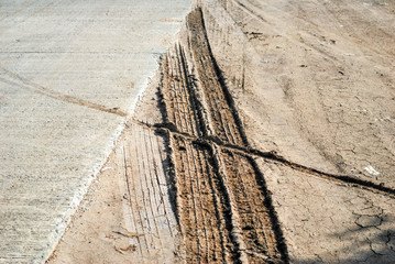 Car tire marks on soil in the rural road