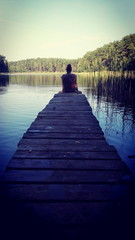Rear View Of Woman Sitting On Jetty Over Lake In Forest