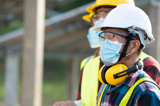 Workers wear protective face masks for safety working in Solar cell Farm through field of solar panels,Corona virus has turned into a global emergency.