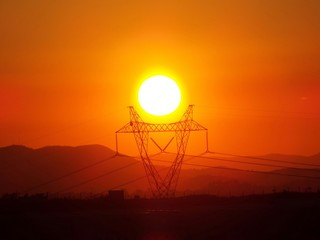 Foto auf AluDibond Ziegel Electricity Pylon On Landscape By Mountains During Sunset