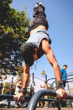 Healthy and fitness young man with cap and wristbands doing calisthenics (inverted pose) on a street workout park on a sunny day with blue sky