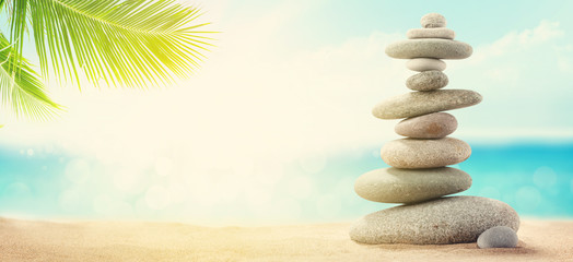 Photo sur Plexiglas Zen pierres a sable Pyramid of sea pebbles on a sunny sand beach