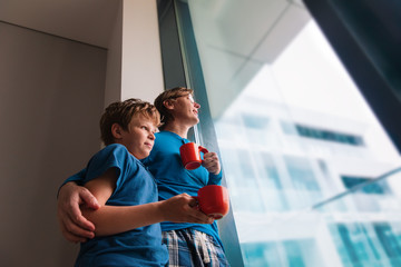father and son looking at window while staying home