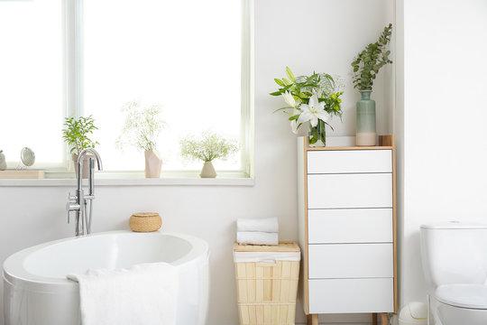 Interior of modern bathroom with floral decor