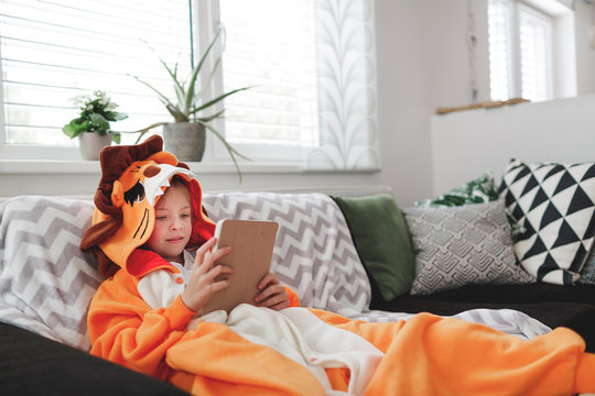 beautiful young Girl with lion costume plays with mobile phone or tablet at home