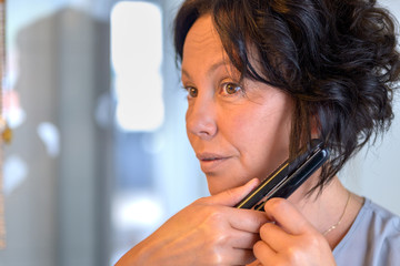 Middle-aged Hispanic woman using curling tongs