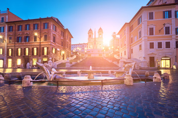 Monumental staircase Spanish Steps and and Trinita dei Monti church, sunrise, dawn, early morning view with Sun flare from Piazza di Spagna in Rome, Italy