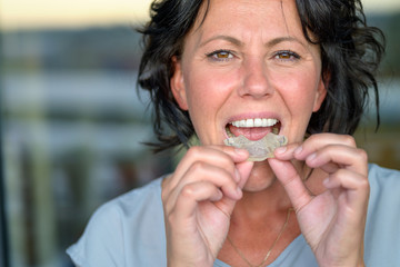 Woman with bruxism holding a mouth guard