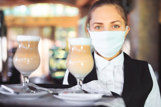 bartender in medical mask and gloves makes latte coffee.