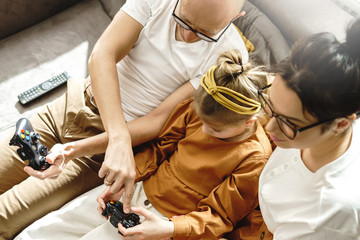 Happy family is playing video game console at home