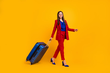 Fototapete - Full body profile photo of classy business lady walk airport flight registration rolling big suitcase wear specs red luxury blazer blouse pants suit shoes isolated yellow color background