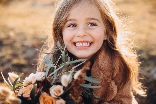 Portrait of a small stylish beautiful model girl who stands in the autumn mountains at sunset and holds a bouquet of flowers in her hands