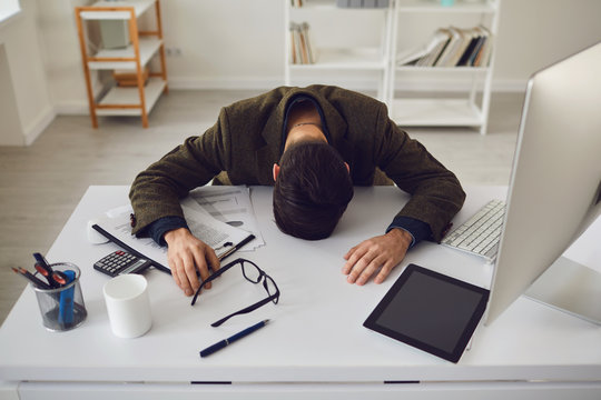 Businessman tired exhausted with stress problems lying at the workplace in the office.