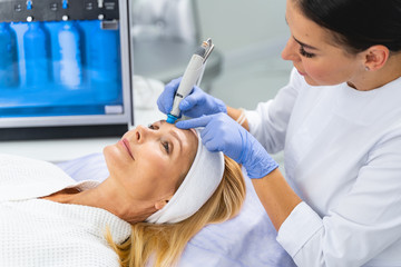 Professional female cosmetologist performing a microdermabrasion treatment