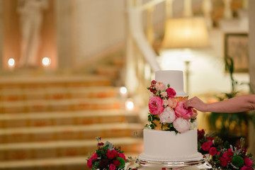 A wedding cake decorated with flowers. Woman makes final adjustments to bouquet, luxury hotel staircase in the background.