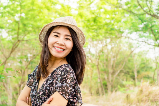 beautiful asian woman age 40s wearing a hat and smiling outdoors in green park