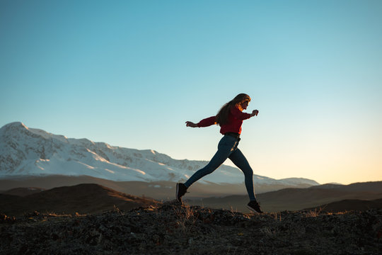 Slim sporty girl walks at sunset in mountains
