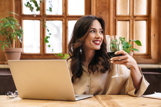 Image of cheerful adult woman drinking red wine and working with laptop